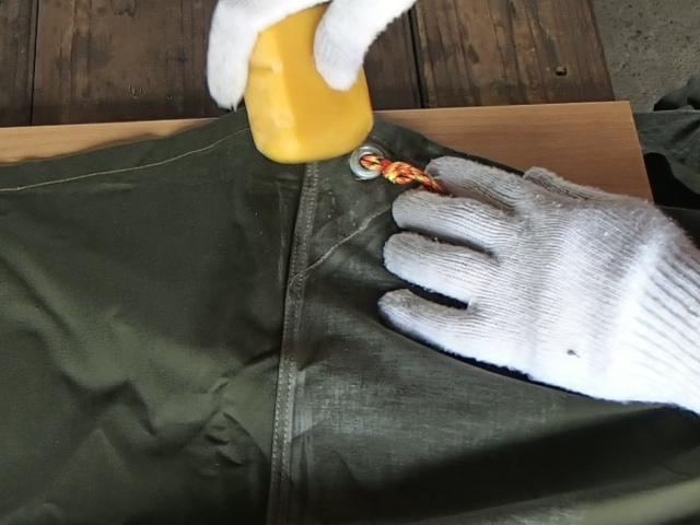 丁寧に自家製グリーンランドワックスをポーランド軍テントに塗っていきます。