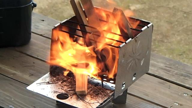 ウッドストーブ(スターノ・フォールディング・キャンプ・ストーブ)に薪を入れ火を強くする