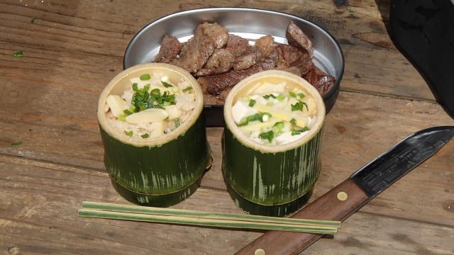 竹の器に盛った筍ごはんと飯盒の蓋に持ったチャックロール(牛肩ロース肉)