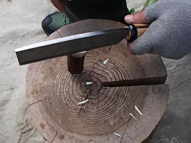竹水筒の栓を作るためにナタで木の枝を割る